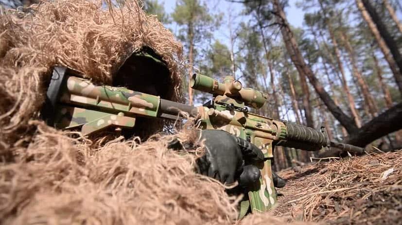 paintball sniper hiding under bushes
